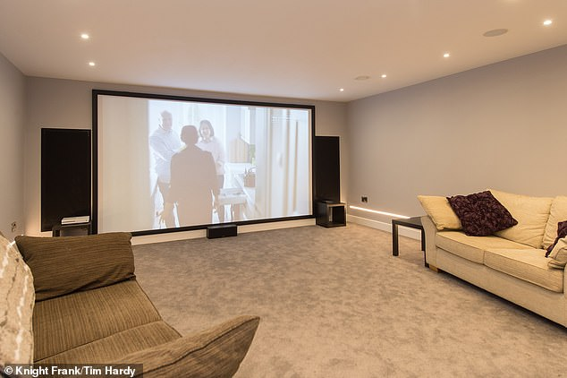 There is a cinema room with a large screen, speakers and seating
