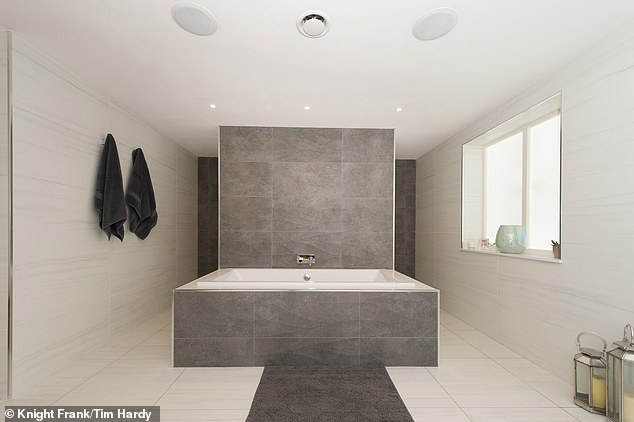The ultra-modern home has eight bathrooms, including this one with grey tiles