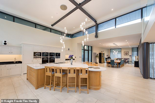 Above the kitchen is a mezzanine level with a a glass galleried balcony