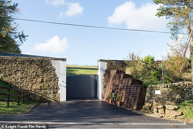 The house is accessed via a sliding electric gate in the retained side wall of the reservoir