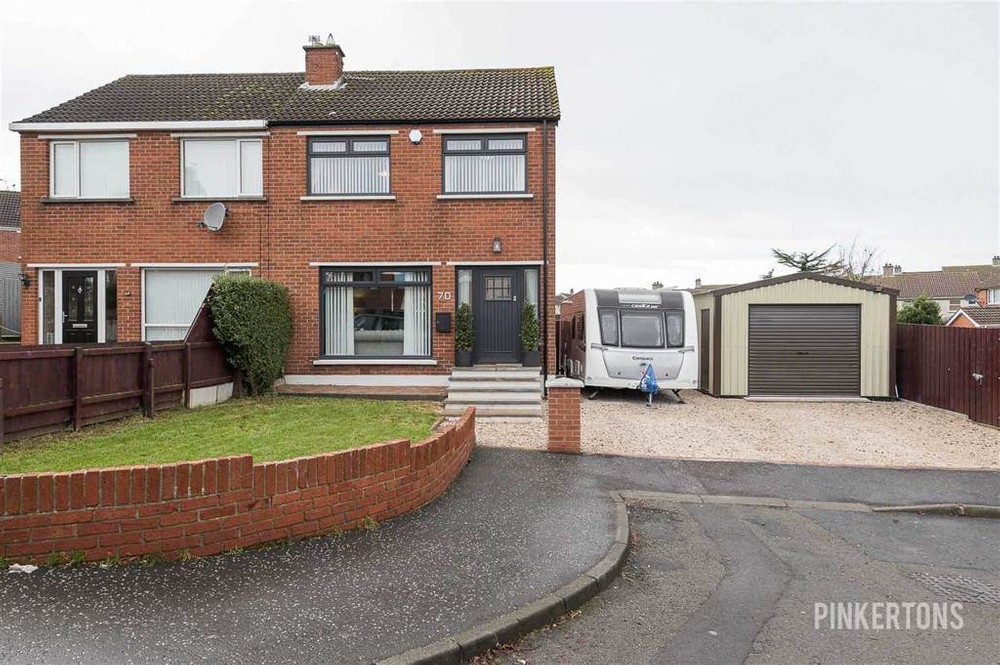 The exterior of 70 Copeland Crescent. This is a red brick, semi-detached house for sale in Comber. A mobile home and garage can be seen to the right of the property.