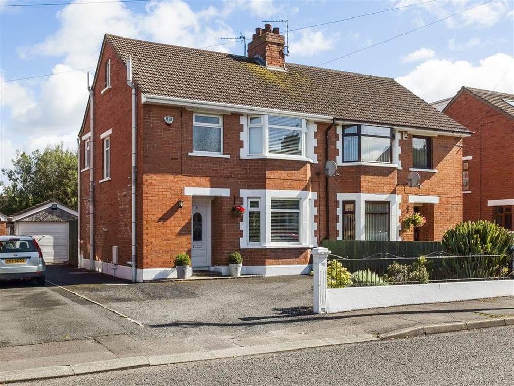 The exterior of 6 Orpen Avenue. This is a red brick semi-detached house for sale in Belfast. There is a bay window on the ground and first floor. A driveway runs along the left side of the house to the garage. An array of plants and shrubs can also be seen in the garden.