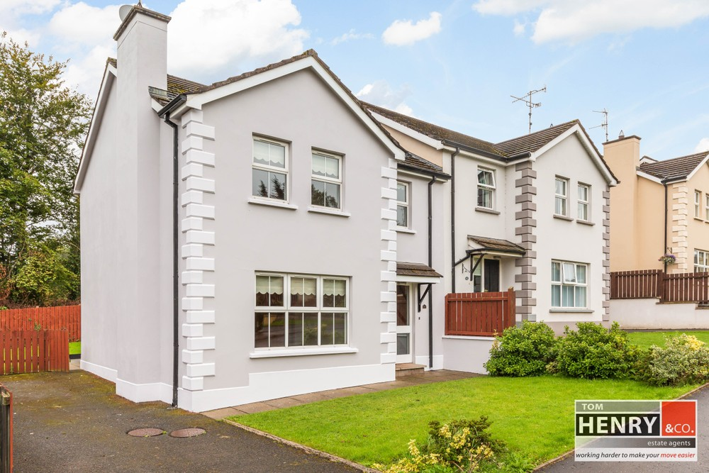 The exterior of 38 The Vale. This is a semi-detached house for sale on the outskirts of Dungannon. A tarmac driveway is found to the left of the property while a well-maintained lawn with shrubs is found to the front of the property.