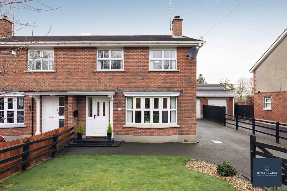 The exterior of 50 Rathfriland Road. This is a semi-detached house for sale in Dromara. A tarmac driveway runs along the right side of the house where a garage is found. A neat lawn is found to the front of the property.