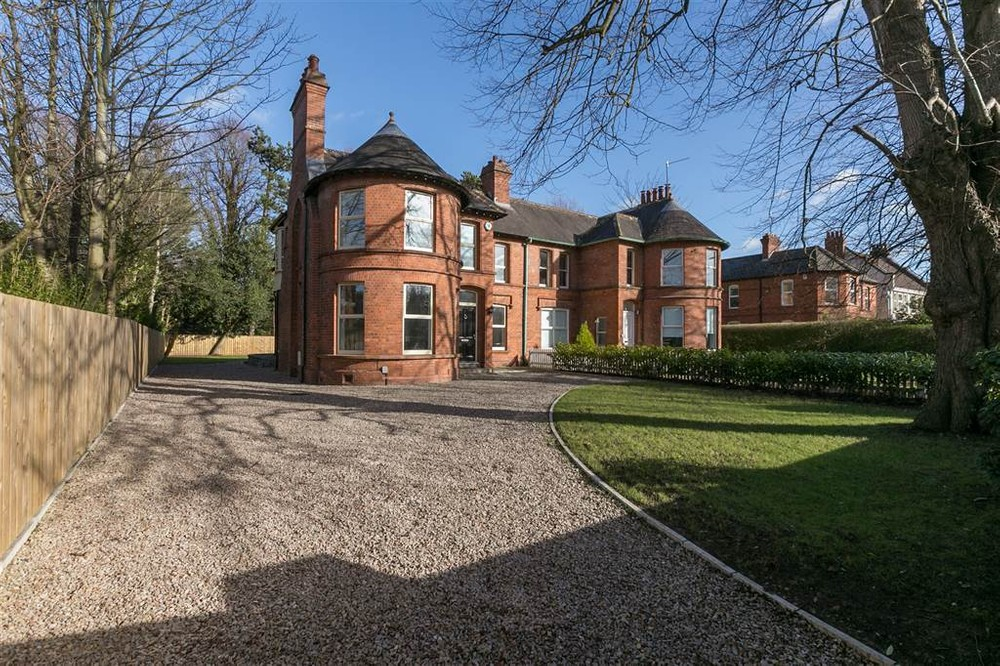 The exterior of 84 Balmoral Avenue. This is a red brick semi-detached house for sale in Belfast. A pebble driveway leads to the front of the house. To the right of the driveway is a well maintained lawn.