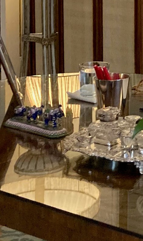 Pictured, trio of blue ornamental elephants, silver tray and silver tub of red pens on Camilla's desk