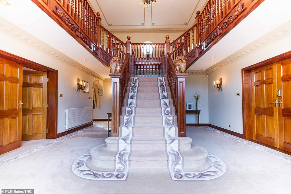 The entrance hallway of the four-bedroom mansion in Bolton, Lancashire, with two wooden figures seen bearing the Manchester United and England crests. Estate agent PLM Sales has asked for a price on application (POA), however the 35-acre property has previously been valued at around £3million