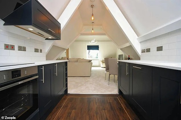 The apartment for sale has a large open plan living area that includes a kitchen with black units