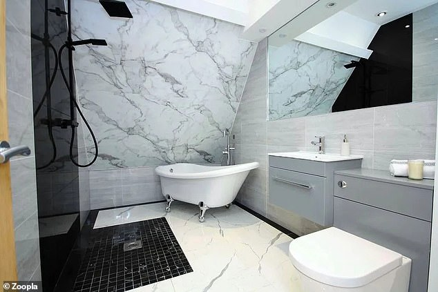 The modern bathroom has a roll top bath, grey units and black fixtures and fittings