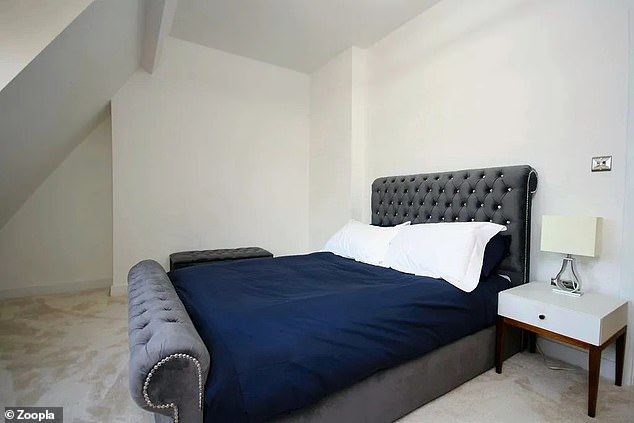 The flat has a large bedroom with a sloping roof line and a window looking out onto the estate