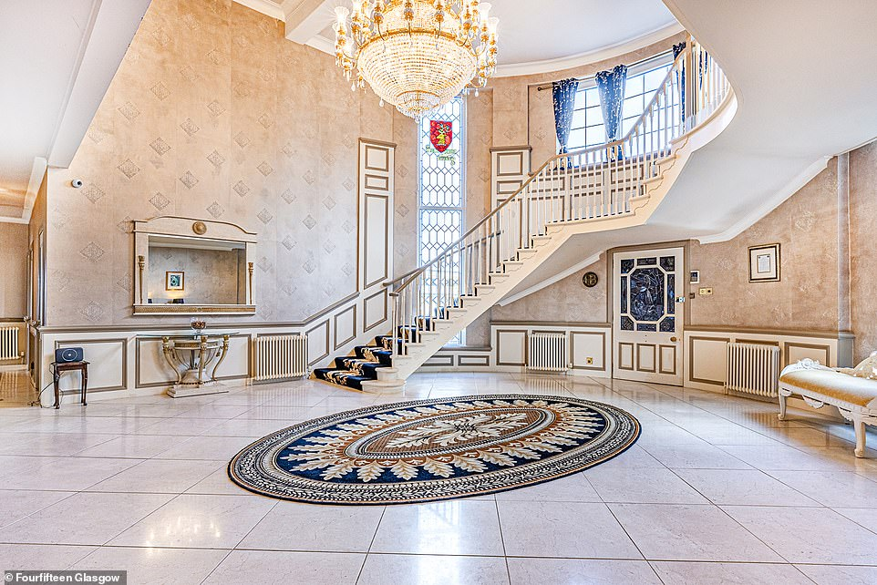 The interior of the property includes a grand sweeping staircase in the entrance hallway that winds around the curved wall