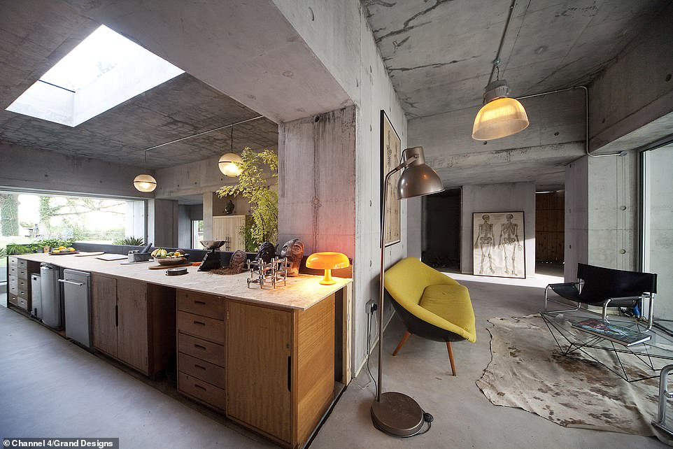BEFORE: The couple's industrial chic property is built entirely using concrete. They raised eyebrows from Kevin McCloud when they revealed they would not polish the walls or even use paint or plaster. Pictured, the property's kitchen and reception space in October 2018, when it was still not watertight and didn't have any heating