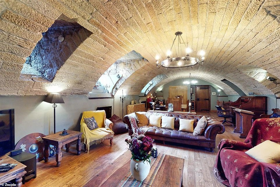 The usual living area has wooden flooring, painted walls, and a large chandelier hanging from the stone ceiling