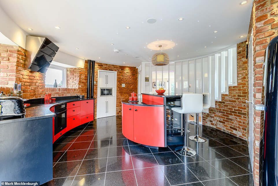 The unusual property has a brightly coloured bespoke fitted circular kitchen, as well as four double bedrooms